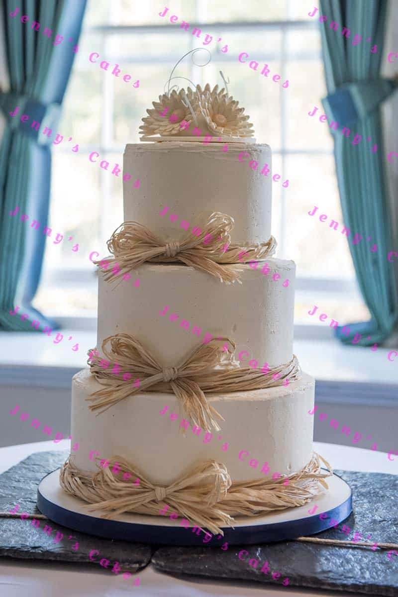 Wedding cake in smooth butter cream with raffia bows